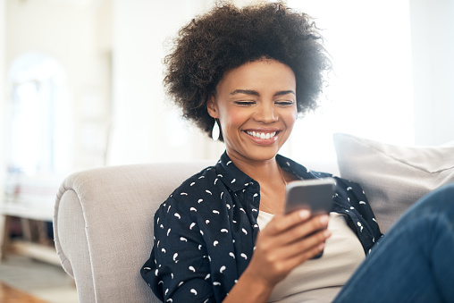 Black woman smiling and looking at cell phone on couch